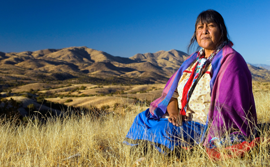 "Ofelia Uya Rivas, an advocate for the cultural and ecological heritage of her people and land for many years, sits by the proposed mine site after performing what she describes as ""a ceremonial offering to the land and ancient ancestors in recognition of the sacredness of the significant O'odham legacy of survival since millennia."" Behind Ofelia rest dozens of significant prehistoric sites, including an ancestral ball court site, traditionally used for games and ceremonies. Most of these sites, including much of the area shown in this photograph, would be buried under hundreds of feet of mine waste. photo: Josh Schachter"